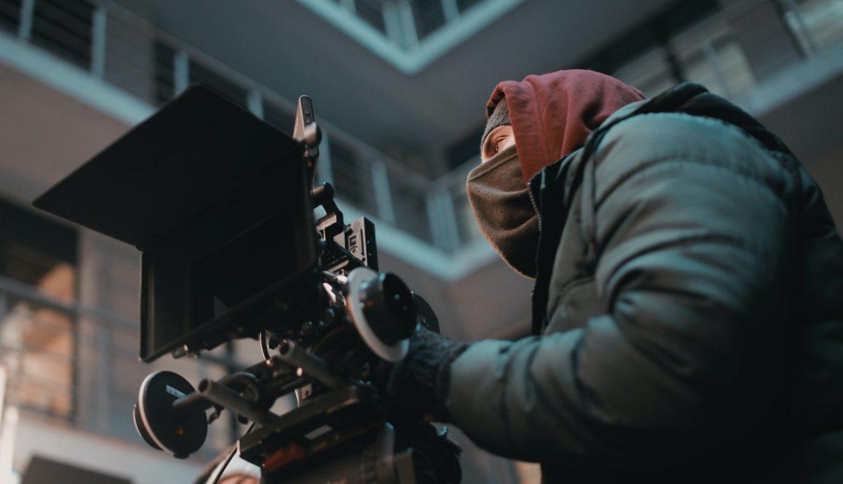 caméraman derrière sa caméra en train de cadrer sur un tournage
